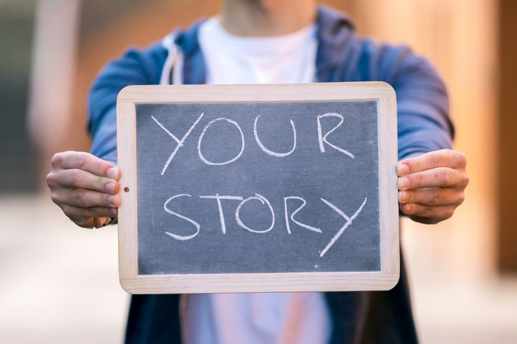 """A storyteller dressed with a white t-shirt and blue sweatshirt is holding a clay slate saying """"your story"""" storytelling"""